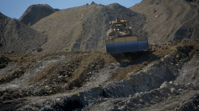 Bulldozer reverses over the crest of a hill video