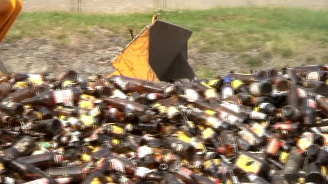 Bulldozer ausschöpfen amber Flaschen in Glas Erholung plant, Nahaufnahme – Video