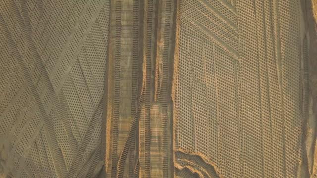 bulldozer spuren. zusammenrücken. baustelle auf der straßenbaustelle. bulldozer dubs sand und boden an einem sommerabend bei sonnenuntergang. luftbild - aerial overview soil stock-videos und b-roll-filmmaterial