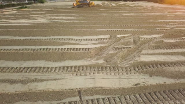 Bulldozer tracks. Close up. Construction site on the road construction site. Bulldozer dubs sand and soil on a summer evening at sunset. Aerial view Bulldozer tracks. Close up. Construction site on the road construction site. Bulldozer dubs sand and soil on a summer evening at sunset. Aerial view construction vehicle stock videos & royalty-free footage