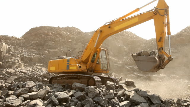 Bulldozer working at mining site loading stone on a truck video
