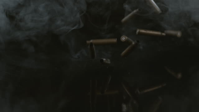 Bullet shells and smoke falling in slow motion