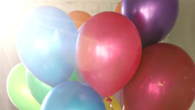 Bunch colorful helium balloons sunlight unfocused Bunch of colorful helium balloons on a bricky white wall background. Colorful balls in the sunlight unfocused happy birthday stock videos & royalty-free footage