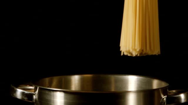 lento : un casco di spaghetti cade in una pentola in acciaio - chef triste video stock e b–roll