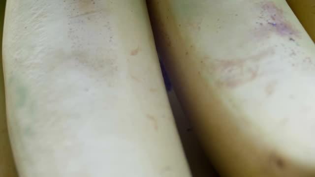 bir salkım muzu sarı kabuğuna beyaz arka plan makro görünümü kapat - penis stok videoları ve detay görüntü çekimi