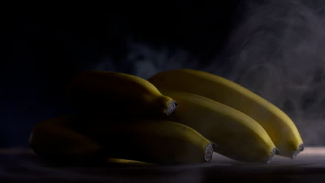 bunch of cavendish bananas are on the table in cold, steam from frost in slowmo, cloese up - acqua ghiacciata video stock e b–roll