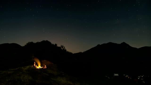 ein haufen freunde sitzen am lagerfeuer in sternenhimmel mit sternen im sommer natur zeitraffer - slowakei stock-videos und b-roll-filmmaterial