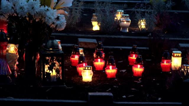 vídeos y material grabado en eventos de stock de hay un montón de velas de cristal en el oscuro cementerio. - memorial day
