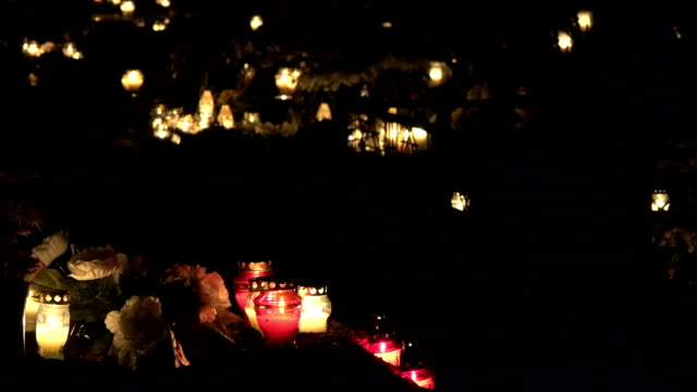 vídeos y material grabado en eventos de stock de hay un montón de vidrio velas coloridas en el cementerio de noche. cambio de enfoque. - memorial day