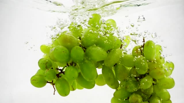 bunch of green grapes falling into water with bubbles in slow motion. berries on white background. - soczysty filmów i materiałów b-roll