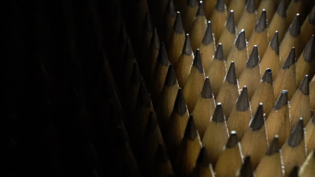 Bunch of identical graphite pencils in rotation on black background video