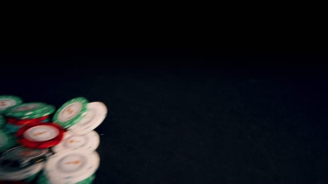 A bunch of poker chips slide out onto a black background on a wide angle lens.