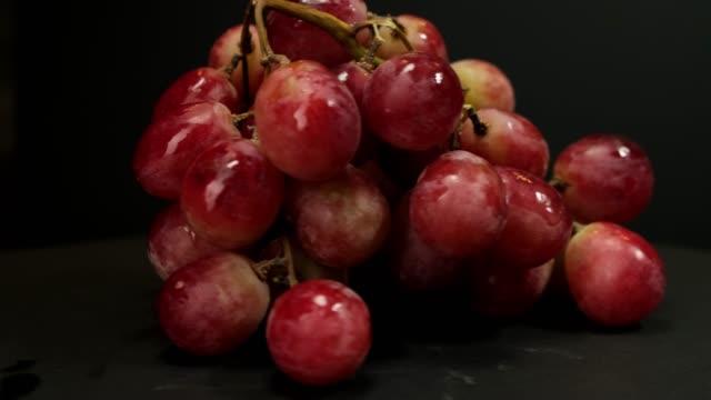 熟した赤ブドウの束は黒い背景に回転します。 - ぶどう イラスト点の映像素材/bロール