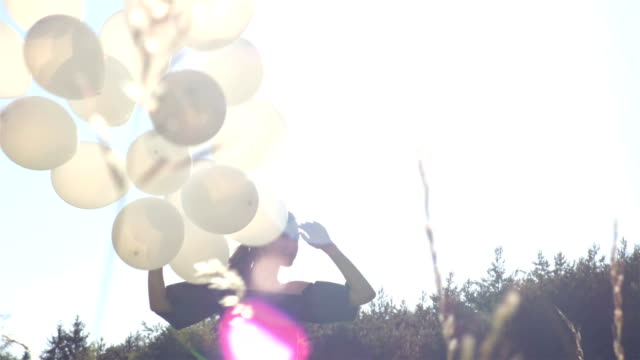 Bunch of white balloons with the girl on the sunny background video