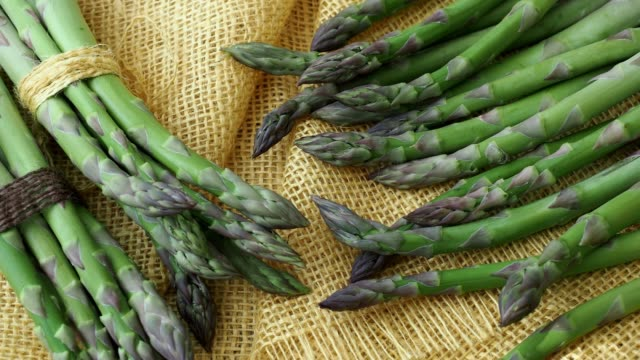Bunches of asparagus tied with twine on a burlap background. Asparagus officinalis. Bunches of asparagus tied with twine on a burlap background. Asparagus officinalis. bunch stock videos & royalty-free footage
