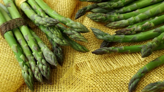 Bunches of asparagus tied with twine on a burlap background. Asparagus officinalis. video