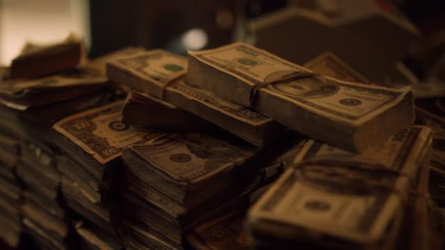 pacchetti di contanti sul tavolo. dolly ha sparato di mucchio di banconote americane, fascio di denaro. il dollaro usa è la valuta ufficiale degli stati uniti d'america - catasta video stock e b–roll