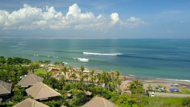 AERIAL: Bungalows in luxury tourist resort overlooking ocean and exotic beach video