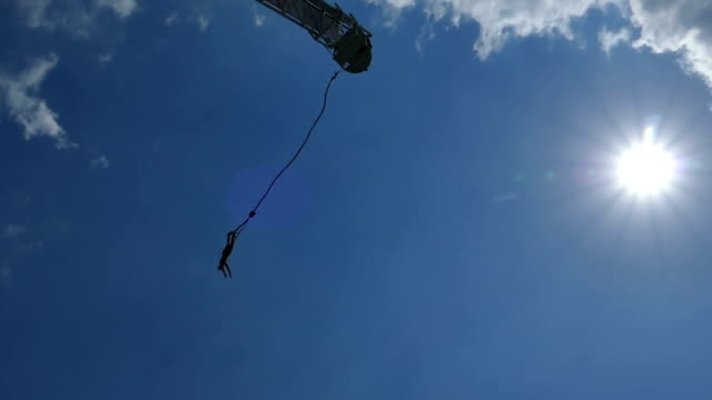 bungee jump released against sun- slow motion - bungee jumping video stock e b–roll