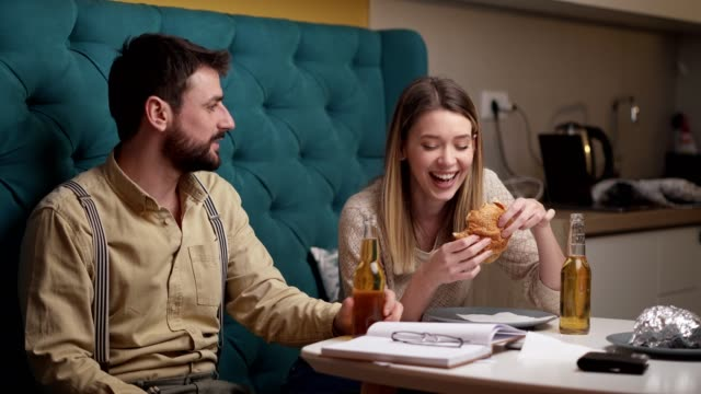 Burger, beer and lots og laugh? I call that a perfect date Charming young couple, drinking beer from the bottle and eating burgers while having so much fun together in their apartment falling in love stock videos & royalty-free footage