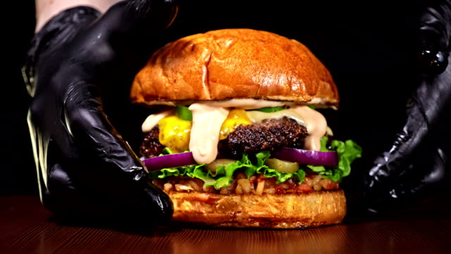 Burger is cooking on black background in black food gloves. Very luscious air bun and marbled beef. Restaurant where each burgers is cooked by hand. Not made ideal. Looks real, loving hand made. video