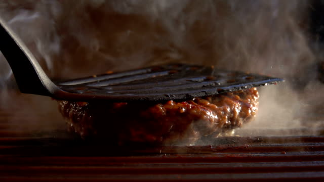 Burger is pressed by kitchen spatula to the grill - video