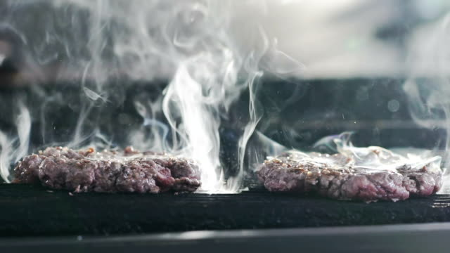 Burger on a grill. Slow motion video
