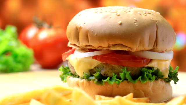 Burger on wooden plate with french fries and vegetables video