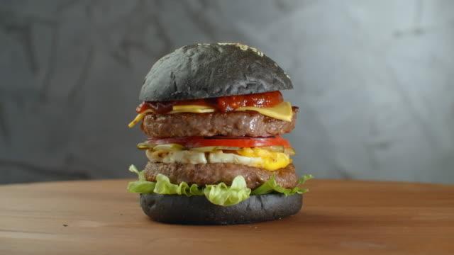 나뭇잎의 흐릿한 배경에 검은 빵을 곁들인 햄버거 나 햄버거. - burger and chicken 스톡 비디오 및 b-롤 화면