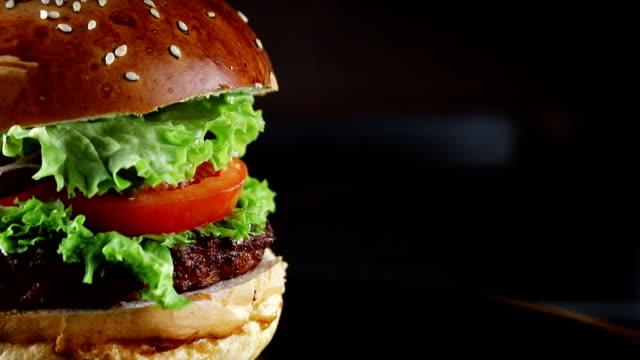 토마토와 허브의 커 틀 릿이 있는 버거는 나무 보드에서 회전 합니다. 검은 배경에서. - burger and chicken 스톡 비디오 및 b-롤 화면