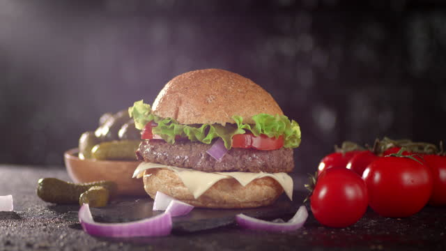 Burger with beef, tomatoes and pickled cucumbers rotates.