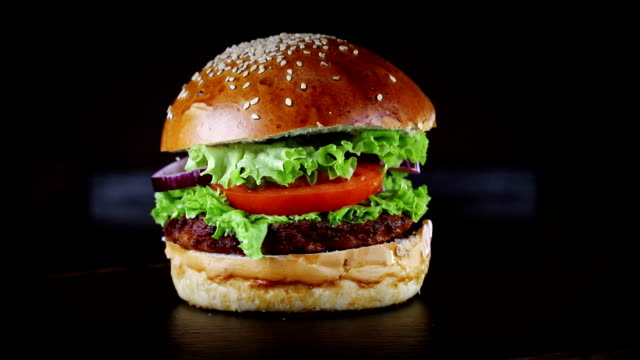 까 스가 있는 버거는 검은 바탕에 나무 판자로 회전 합니다. - burger and chicken 스톡 비디오 및 b-롤 화면