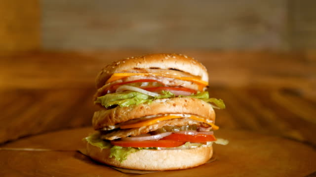 A burger with two cutlets and vegetables lies on a piece of wood. Unhealthy food. Professionally cooked fast food.