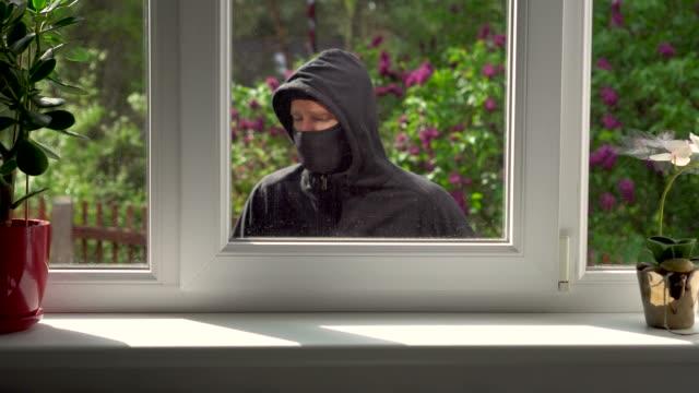 vídeos de stock e filmes b-roll de burglar breaks into a house through the window - ladrão