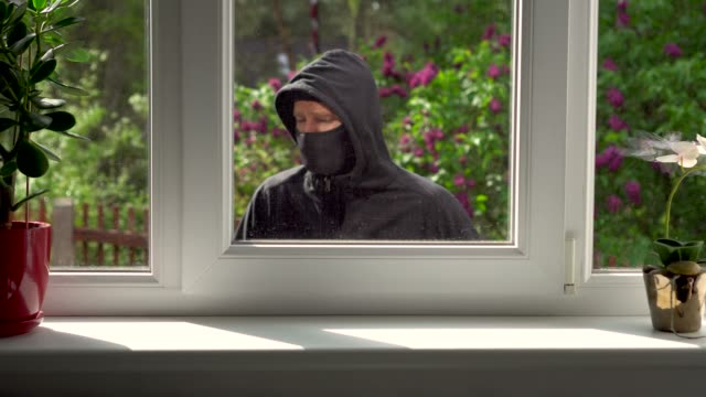 burglar breaks into a house through the window - вор стоковые видео и кадры b-roll
