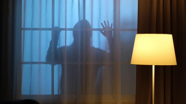 Burglar outside the window with a knife.
