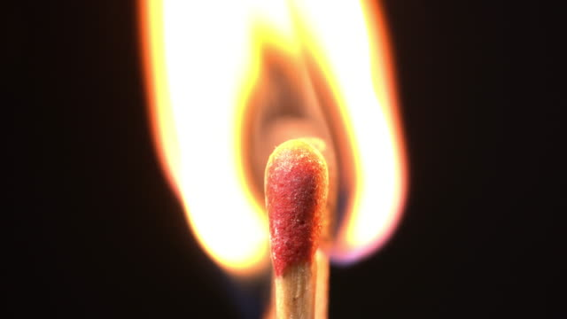 A burning a group of match sticks in black background.