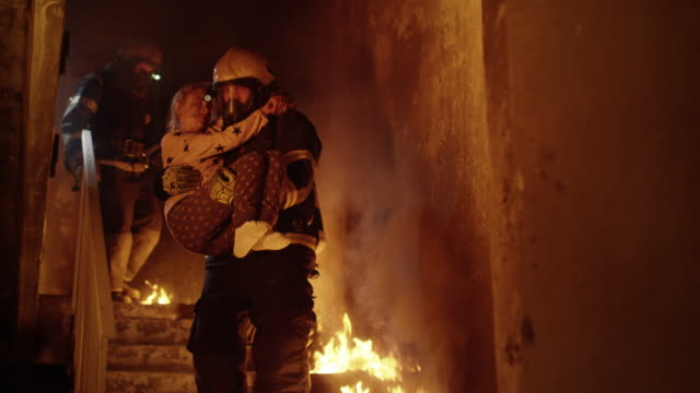 vídeos de stock e filmes b-roll de burning building. group of firemen descend on burning stairs. one fireman holds saved girl in his arms. - resgate