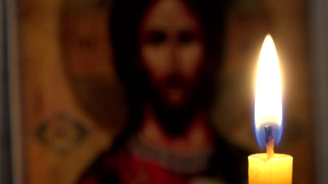 A burning candle against the background of orthodox icons in a dark room A burning candle against the background of orthodox icons in a dark room candle stock videos & royalty-free footage