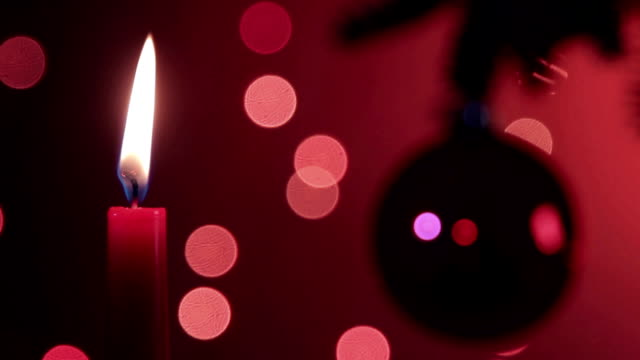 Burning candle and Christmas tree with ornament in nice ambient video