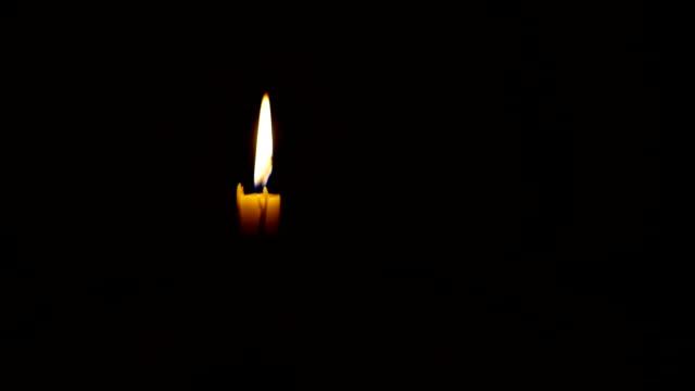 brennende kerze in der dunkelheit - mahnwachen stock-videos und b-roll-filmmaterial