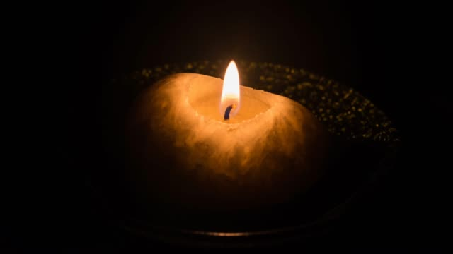 Burning candle on a plate isolated on a black background