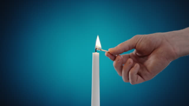 burning candle on a red background video