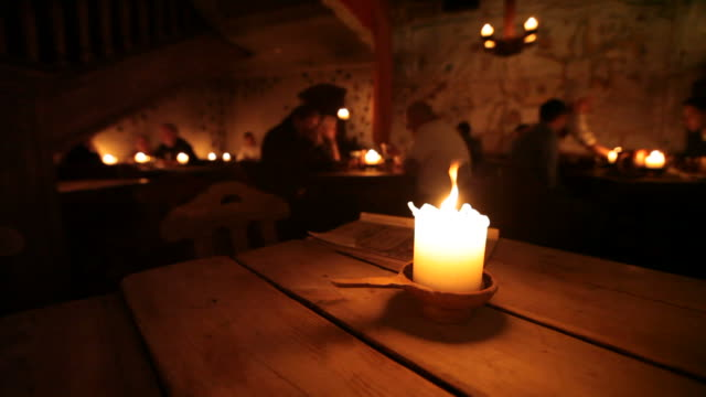 Burning candle on a wooden table in old restaurant of Tallinn, Estonia video