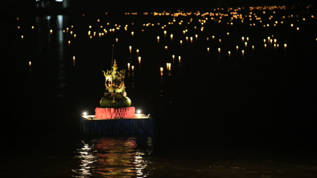 Burning candles float on water during Loi Khrathong celebration in Thailand. video