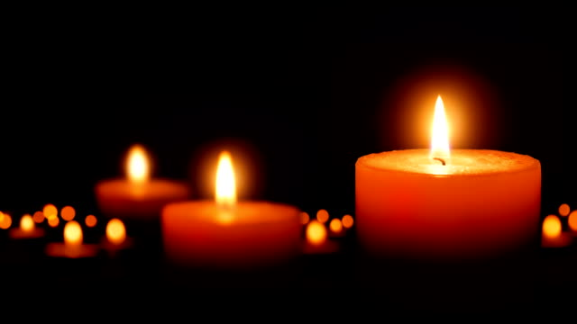 Burning candles gently glowing in the dark