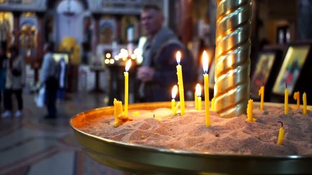 vídeos y material grabado en eventos de stock de quemando velas en el templo de la iglesia - misa