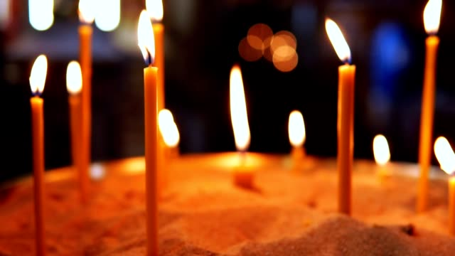 Burning candles inserted in the sand in the Orthodox Church