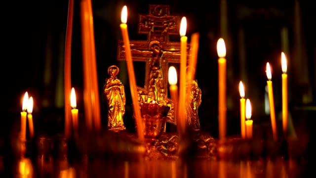 brinnande ljus på bakgrund av den gyllene korsfästelsen av jesus kristus - stavning bildbanksvideor och videomaterial från bakom kulisserna