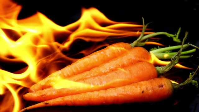 Burning carrot on black background slow motion Burning carrot on black background slow motion menu stock videos & royalty-free footage